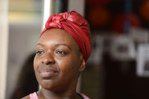 Nicéa Quintino, mulher negra de turbante vermelho, olhando para o lado