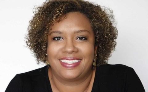Carla Sena, mulher negra de cabelo cacheado, sorrindo.