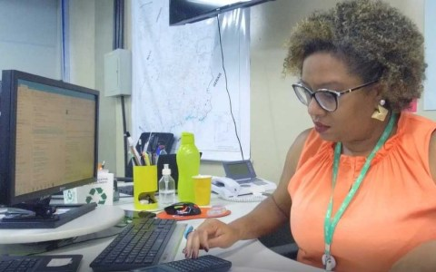 Carla Sena, mulher negra de cabelo cacheado, sentada em frente ao computador.