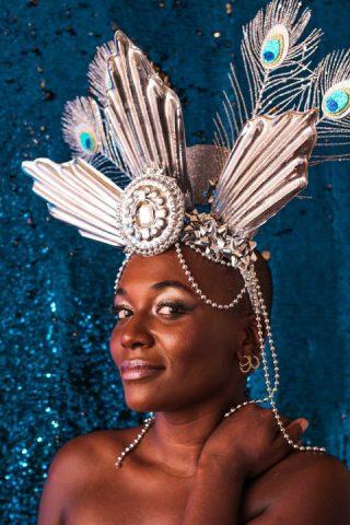 Mulher negra de cabelos raspado, em pé com fantasia característica de carnaval,