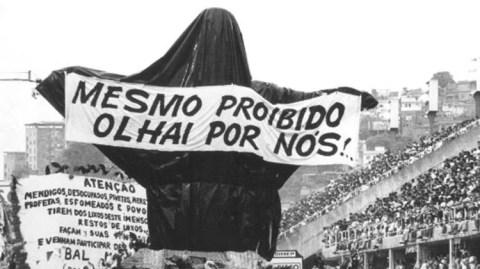 """Imagem em preto e branco que mostra um dos carros alegóricos da Beija-Flor, onde se tem o cristo redentor coberto com uma lona preta e um cartaz pendurado em seus braços escrito """"Mesmo proibido olhai por nós!"""""""