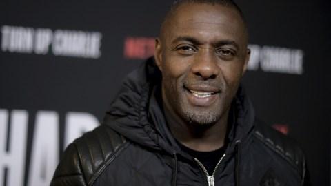 Ator Idris Elba, homem negro careca, em pé pousando para uma foto