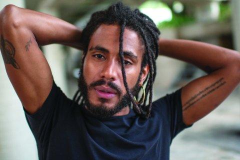 Ícaro Silva- homem negro, com barba e dreads- em pé fazendo pose para foto.