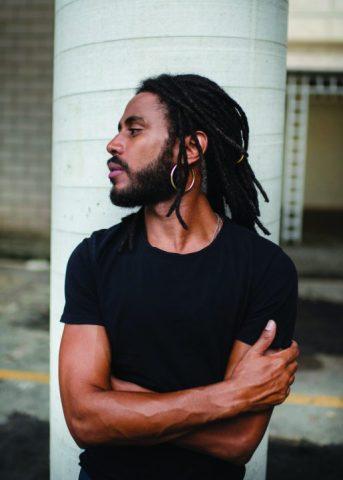 Ícaro Silva- homem negro, de barba e dreas- pousando para uma foto