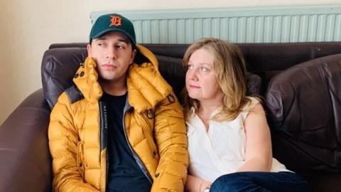 Sue, mulher branca e loira, sentada no sofá de couro marrom com seu filho Morgan Elliott, homem branco. Sue veste camiseta branca e calça azul escura enquanto Morgan veste casaco amarelo e boné verde.