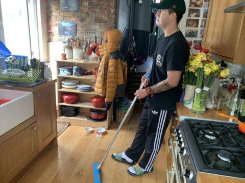 Morgan- homem branco de 23 anos, vestindo roupas toda preta- na cozinha com um rodo na mão