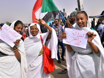 Mulheres sudaneses com cartazes nas mãos.