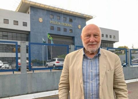 Domenico De Masi, homem idoso branco calvo, em pé na frente de um quartel da policia federal brasileira