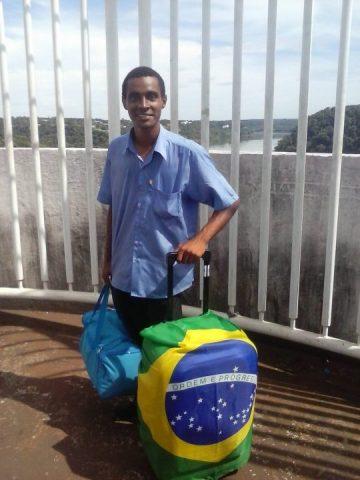 Jefferson Dionísio de Souza, homem negro, em pé com uma mala de viagem com a bandeira do Brasil.