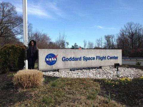 """Carolayne de Oliveira, ao lado de uma estrutura indicando o centro de pesquisa da NASA. A estrutura possui o simbolo da NASA  e a frase """"Goddard Space Flight Center"""""""