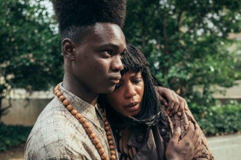 jovem negro abraçado com uma mulher chorando, negra de cabelo com tranças,