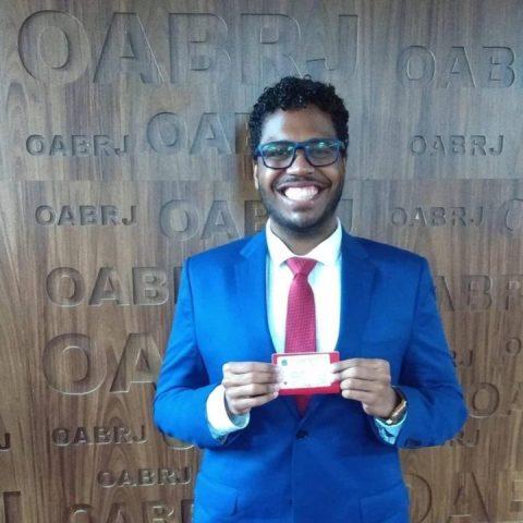 Felipe Rigueira- homem negro de terno e usando óculos- sorrindo na sede da OAB do Rio de Janeiro, com a sua carteira de advogado na mão.