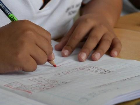Imagem de uuma mão escrevendo em um caderno.