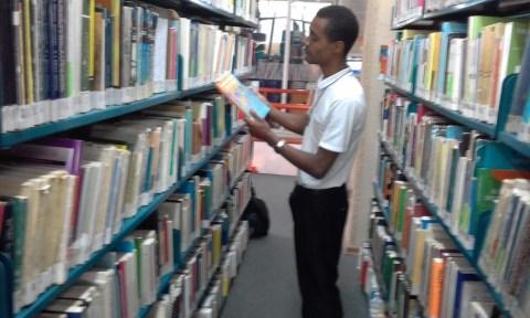 Jefferson Dionísio de Souza, em uma biblioteca com um livro na mão.