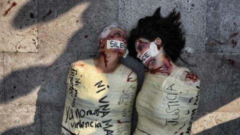 """Duas mulheres deitadas no chão, com o corpo todo envelopado e diversos hematomas, com boca tampada por um papel escrito """"Silence"""""""
