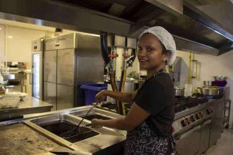 Claudia Santos- mulher negra, com touca na cabeça e vestindo um avental-  cozinhando em uma cozinha de restaurante .