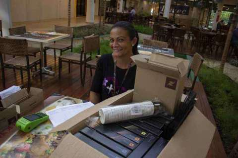 Grasiela Maria de Araújo- mulher negra, de cabelo liso, vestindo blusa de manga preta- sentada em frente a uma mesa cheia de caixas.