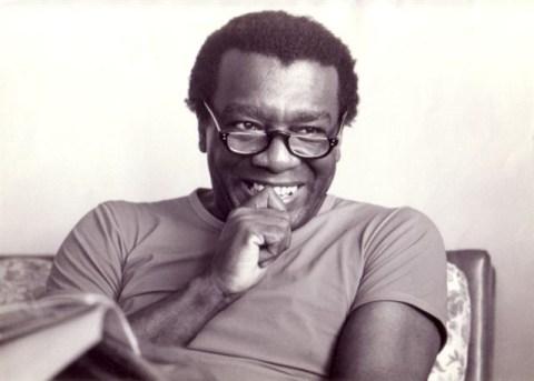 Imagem em preto e branco de Milton Santos- homem negro, vestindo camiseta e óculos de grau- sentado, com um livro na mão esquerda, sorrindo e com a mão direita na boca.