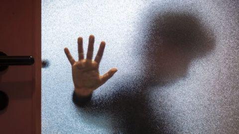 Uma mão apoiada em uma porta de vidro.