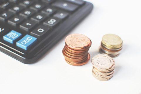 Imagem de uma calculadora e três pilhas de moedas