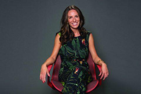 Camilla Junqueira- mulher branca, vestindo um vestido verde escuro com estampa de folhas- sentada em uma cadeira vermelha