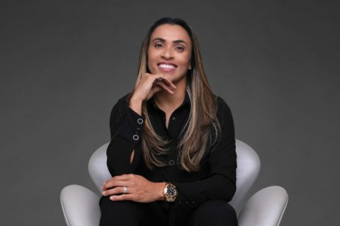 Marta, mulher parda de cabelos longos, vestindo calça e blusa preta, sentada em uma poltrona branca.