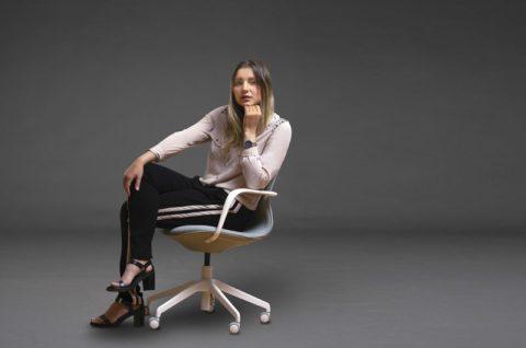 Maya Gabeira- mulher branca de cabelos longos e loiro, vestindo calça preta e camiseta beje- sentada de pernas cruzadas em uma cadeira
