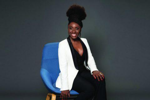 Nina Silva- mulher negra de cabelo crespo, vestindo macacão preto e jaqueta branca- sentada em uma poltrona azul, sorrindo