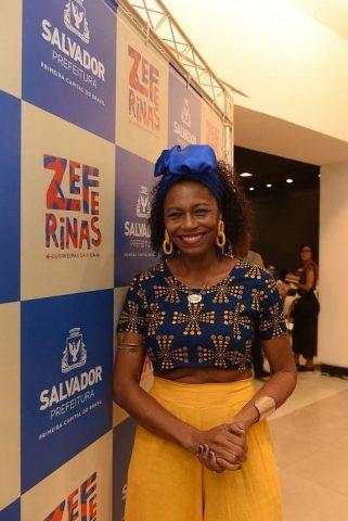 Edvana Carvalho-mulher negra vestindo roupas coloridas -em pé sorrindo,