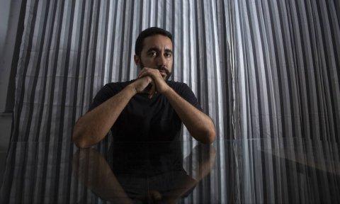 Lucas Lopes- homem pardo de cabelo curto e pouca barba, vestindo camiseta lisa preta- sentado apoiando os braços em uma mesa de vidro e com as mãos em frente a boca.