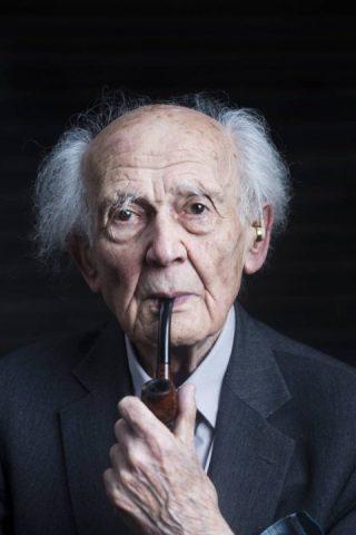 Zygmunt Bauman- homem idoso branco, calvo, vestindo terno cinca escuro- fumando um charuto.