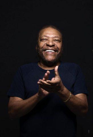 Martinho da Vila- homem idoso negro, vestindo camiseta lisa azul- batendo palmas e sorrindo.