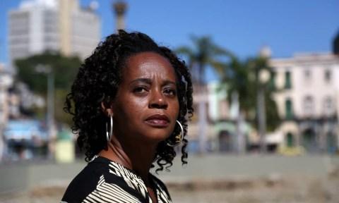 Eliana Alves Cruz- mulher negra, de cabelo cacheado, vestindo camiseta listrada preto e branca- sentada olhando para o horizonte.