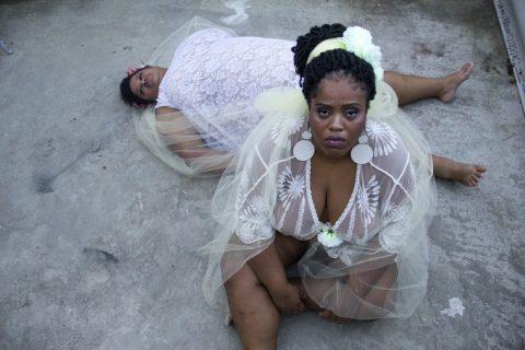 Duas mulheres negras vestindo roupas branca. Uma mulher esta sentada no chão e a outra deitada no chão .