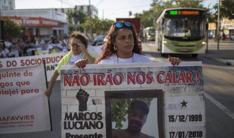 """Bruna Mozer - mulher parda de cabelo cacheado- segurando um cartaz escrito """"Não vamos nos calar!"""" com a foto de seu filho, Marcos Luciano, e a data da morte dele (15/12/1999- 17/02/2018)"""