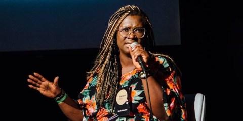 Selma Dealdina- mulher negra, vestindo camiseta colorida- sentada discursando com um microfone na mão esquerda