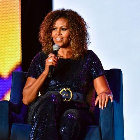 Michelle Obama - mulher negra, de cabelo cacheado vestindo um macacão preto de paete.