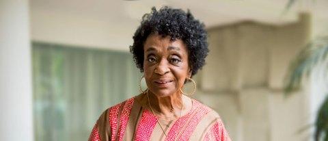 Léa Garcia- mulher idosa negra, de cabelo curto e cacheado, vestindo camiseta colorida- em pé olhando para rente e sorrindo