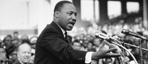 Martin Luther King - homem negro, de pouco cabelo, vestindo terno e gravata- durante um discurso
