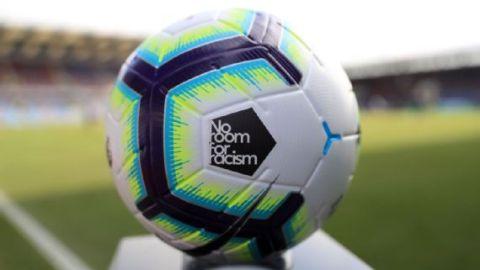 """Uma bola de futebol com a mensagem """"No room for Racism"""" escrita nela"""
