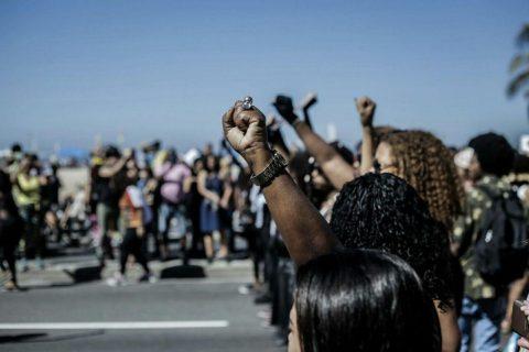 Foto de mulheres negras com os punhos levantados durante uma manifestação
