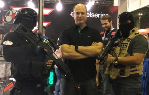 Wilson Witzel - homem branco careca, usando camiseta polo preta e óculos de grau - ao lado de dois homens encapuzados com armas de grande porte nas mãos