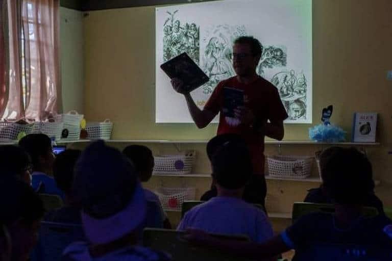 Foto de um professor dando aula em uma sala pouco iluminada
