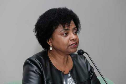 Nilma Lino Gomes- mulher negra, de cabelo cacheado curto, usando camiseta estampada e jaqueta preta- sentada diante de um microfone