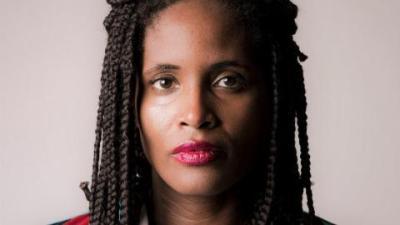 Djamila Ribeiro- mulher negra, de tranca, usando batom vermelho- olhando para frente