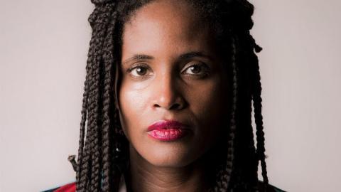 Djamila Ribeiro- mulher negra, usando tranças e batom vermelho- olhando para frente