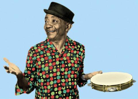Foto de Jackson do Pandeiro- homem idoso negro, vestindo camiseta estampada cheia de bolinhas coloridas e um chapeu- sorrindo com um pandeiro na mão