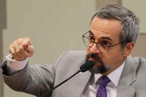 Mistro Weintraub- homem branco, de cabelos e barba grisalhos, usando roupa social e óculos de grau- diante de um microfone gesticulando