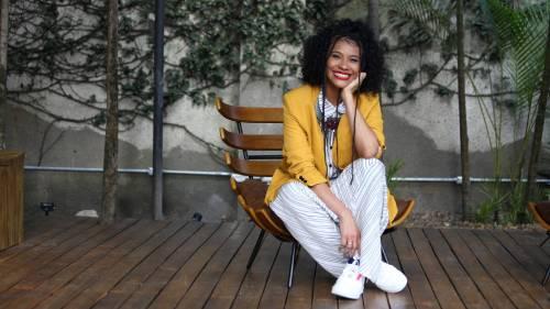 Samantha Almeida- mulher negra, de cabelo cacheado, usando macacão branco e blazer amarelo- sentada sorrindo
