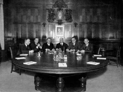 Das Foto zeigt den Vorstand der Dresdner Bank ca. 1937 unter einem Hitler-Portrait. Außen sitzen die beiden SS-Ehrenoffiziere Emil Meyer (links) und Karl Rasche (rechts).